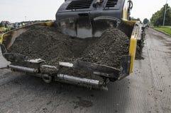 在修路时涂柏油摊铺机机器和修理工作 摊铺机修整机、沥青修整机或者铺的机器 免版税库存照片