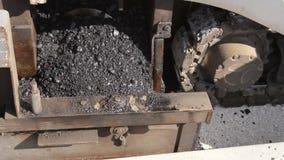 在修路时金属化供应的木钻与在传播的机器的热的沥青 股票录像