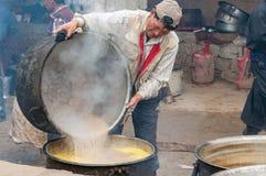 在修道院里烹调印地安黄油茶为佛教仪式做准备 免版税库存照片