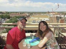 在俯视圣菲的屋顶酒吧的一对夫妇 免版税库存照片