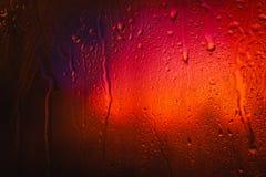 在俯视城市的一个湿窗口的雨珠 图库摄影