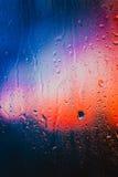 在俯视城市的一个湿窗口的雨珠 免版税库存照片