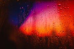 在俯视城市的一个湿窗口的雨珠 库存图片