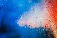 在俯视城市的一个湿窗口的雨珠 库存照片