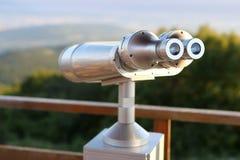 在俯视城市的有利位置的投入硬币后自动操作的双筒望远镜 免版税库存图片