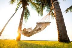 在俯视山的热带棕榈树的吊床 免版税库存图片