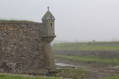 在俯视护城河的Louisburg历史的堡垒的墙壁上的一个警卫塔在一有雾的天 免版税库存照片