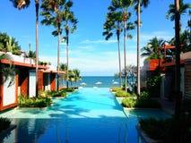 在俯视海滩和海天空的,放松假日假期的一种豪华旅馆手段的游泳池 库存照片