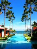 在俯视海滩和海天空的,放松假日假期的一种豪华旅馆手段的游泳池 图库摄影