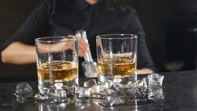 在俱乐部的夜生活 准备在葡萄酒杯的女性男服务员酒精鸡尾酒投入冰立方体在慢动作 冰 影视素材