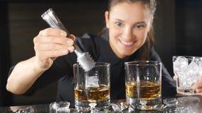 在俱乐部的夜生活 准备在葡萄酒杯的女性男服务员酒精鸡尾酒投入冰立方体在慢动作 冰 股票视频