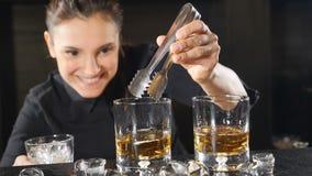 在俱乐部的夜生活 准备在葡萄酒杯的女性男服务员酒精鸡尾酒投入冰立方体在慢动作 冰 股票录像