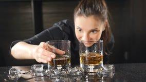 在俱乐部的夜生活 准备在葡萄酒杯的女性男服务员酒精鸡尾酒投入冰立方体在慢动作 ? 股票录像
