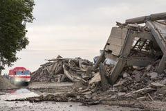 在倒塌的混凝土建筑中的消防队汽车 库存照片