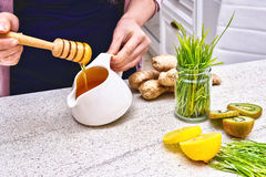 在倒绿色麦子、柠檬和姜戒毒所圆滑的人的滴水的金黄液体有机蜂蜜 库存照片