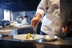 在倾吐的餐馆沙拉的主厨概念食物新鲜的厨房油橄榄 准备传统意大利食物 白色制服的厨师装饰在现代餐馆kitch内部的准备好盘  免版税图库摄影