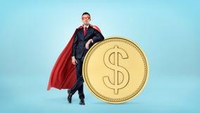 在倾斜在与美元的符号的一枚大金黄硬币的红色海角和眼罩的一个商人 免版税库存图片