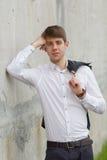 在倾斜在墙壁的白色衬衣的年轻商人 免版税库存图片