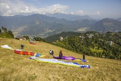 在倾斜的几个滑翔伞准备离开以一座绿色山为背景 库存照片
