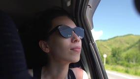 在倾斜车窗的汽车的亚洲女孩太阳镜享用风吹的头发 山背景 股票视频