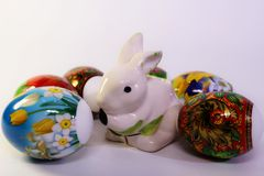 在假日桌上的被绘的鸡蛋围拢的复活节兔子 库存照片