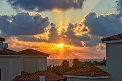 在假日海滩别墅的日落在塞浦路斯海岸 免版税库存图片
