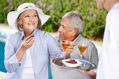 在假日饮用的鸡尾酒的资深夫妇 免版税图库摄影