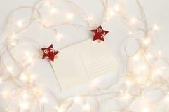 在假日lighs之前围拢的白色背景的空白的明信片 库存图片