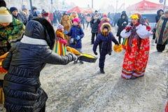 在假日maslenitsa的古老俄国乐趣-在煎锅的投掷的薄煎饼 免版税图库摄影