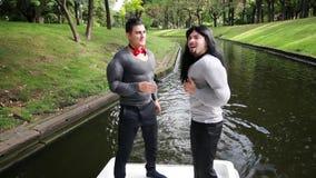 在假肌肉服装打扮的两个可爱的滑稽的人唱歌和跳舞在小船 股票视频