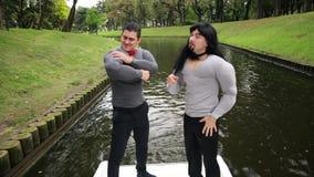 在假肌肉服装打扮的两个英俊的滑稽的人唱歌和跳舞在小船 股票视频