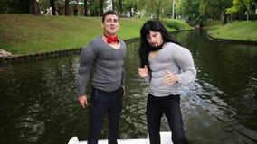 在假肌肉被填塞的服装打扮的两个可爱的人在移动的小船跳舞 股票视频