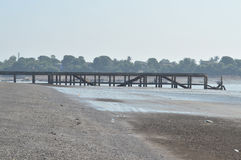 在偏僻的海滨附近的残破的桥梁 免版税库存照片