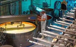 在做一种著名瑞士格里尔干奶酪的一个铜水壶的热化牛奶 免版税库存照片