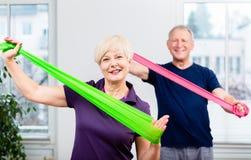 在做与rubb的资深体操类的年长夫妇锻炼 免版税库存图片