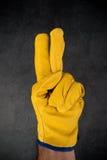在做两个手指Gest的皮革建筑工作手套的手 库存图片