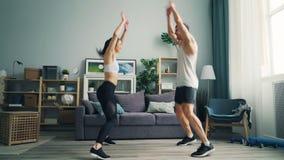 在做体育的运动服的快乐的人夫妇跳跃在家举胳膊 股票录像