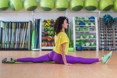在做前面的运动服的俏丽的健身模型在健身房分裂了,舒展她的腿,看照相机和微笑 库存图片