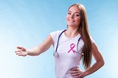 在做受欢迎的姿态的胸口的妇女桃红色丝带 免版税库存图片