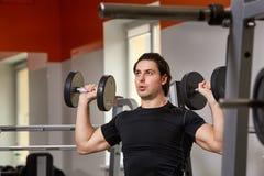 在做坐的哑铃的黑T恤杉的个人教练员为训练他的二头肌卷曲,在健身房 免版税图库摄影