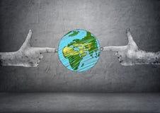 在做射击的两只手拉的手之间的行星地球打手势 库存照片