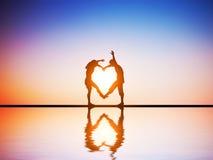 在做心脏的爱的一对愉快的夫妇塑造 免版税库存照片