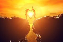 在做心脏的爱的夫妇塑造在悬崖 库存图片
