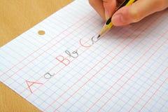 在做文字的孩子的手上的特写镜头 库存图片