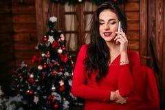 在做电话的圣诞树附近的愉快的少妇 免版税图库摄影