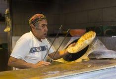 在做皮塔饼面包的一个五颜六色的帽子的一个年长犹太男性在一个小家庭面包店在Mahane耶胡达市场附近在耶路撒冷 库存图片