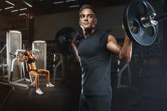 在做锻炼的健身房的年轻和适合的夫妇 库存照片