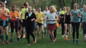 在做锻炼的城市公园的Athlets人群,跑步在一个地方,夏日 股票录像
