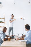 在做介绍的白板的商人对同事 免版税图库摄影