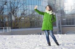 在做selfie的商业中心附近的一个少妇在冬天 免版税库存图片